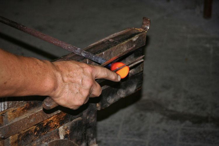 Cropped hand holding work tools in workshop