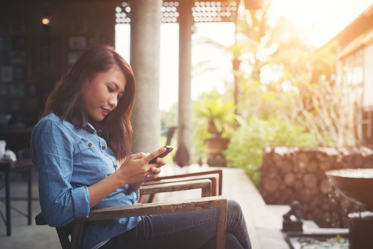Side view of woman using smart phone while sitting at yard