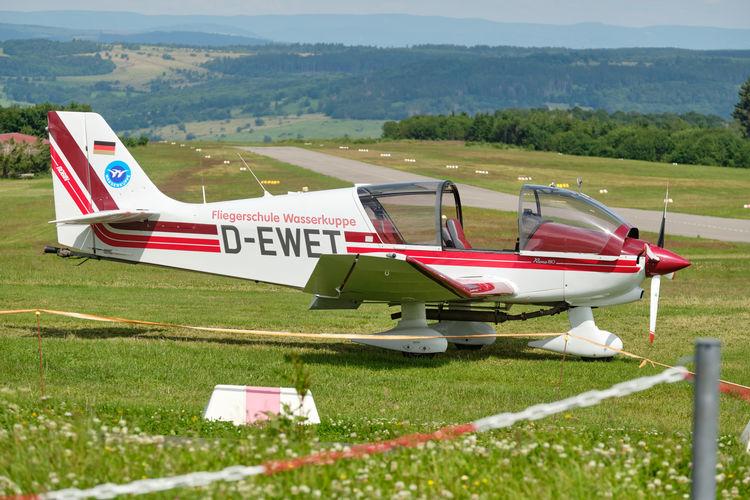 Side view of airplane on runway against sky