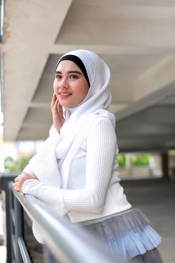 Smiling young woman wearing hijab standing by railing