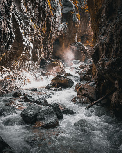 Scenic view of stream flowing by rock formation