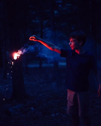 Boy Holding Burning Stick In Forest At Dusk