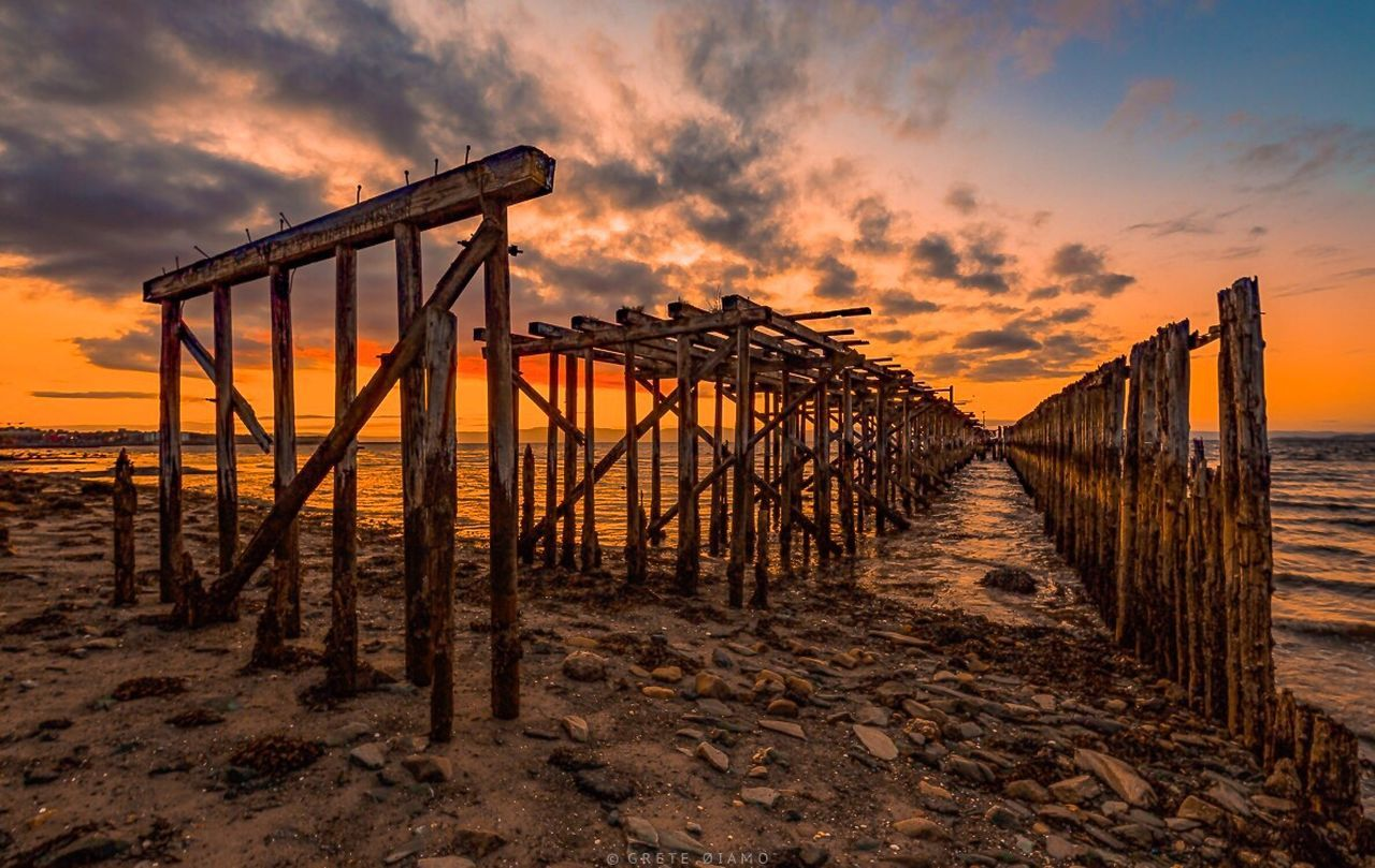 sunset, sky, orange color, cloud - sky, beach, nature, sea, tranquility, outdoors, water, sand, tranquil scene, sun, scenics, beauty in nature, wooden post, no people, horizon over water, day