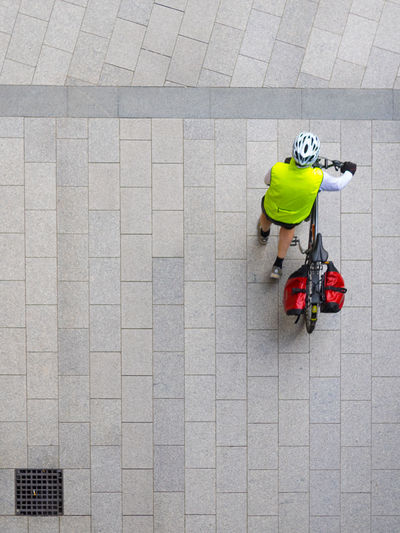 High angle view of man with bicycle on cobbled street