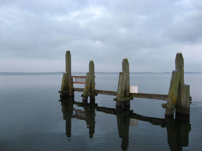 Wooden post in lake against cloudy sky