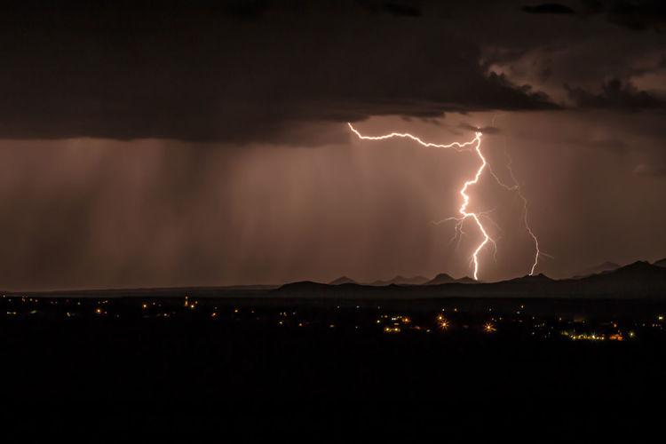 Illuminated cityscape against sky during thunderstorm