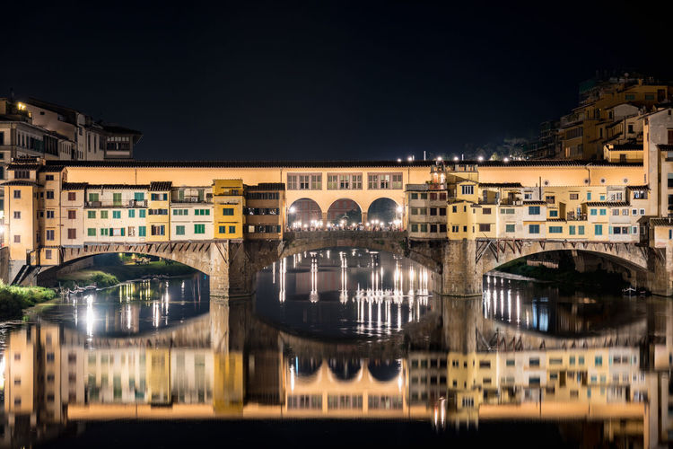 Ponte Vecchio With Reflection Over Arno River Against Sky At Night