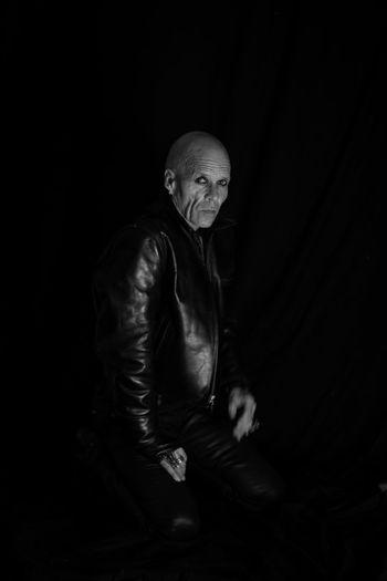 Portrait of man sitting against black background