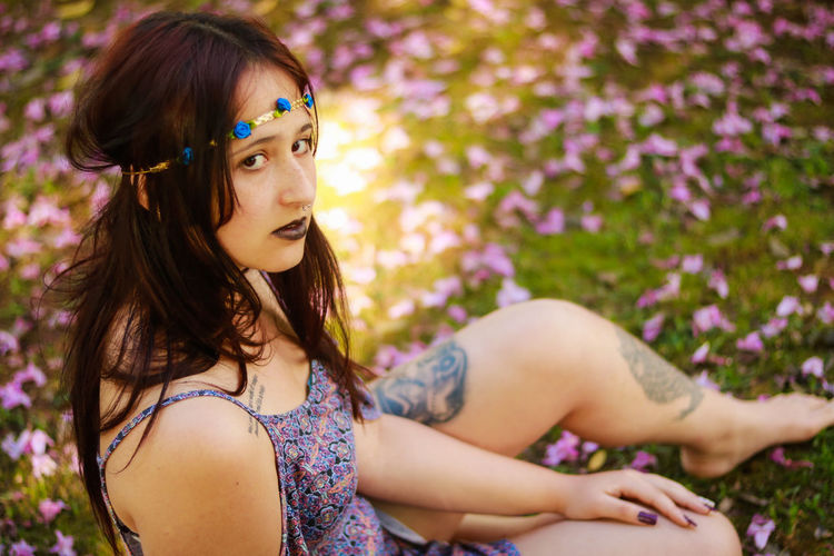 High angle portrait of young woman sitting on flowers in park