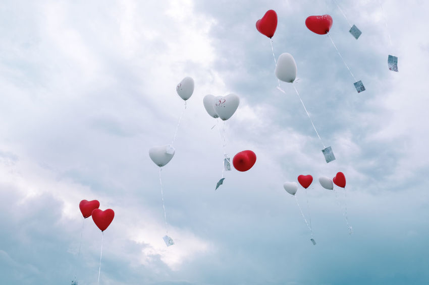 Copy Space Romantic Wedding Balloon Celebration Cloud - Sky Day Flying Freedom Heart Shape Helium Helium Balloon Large Group Of Objects Love Low Angle View Message Mid-air Multi Colored Nature No People Outdoors Positive Emotion Red Sky Variation