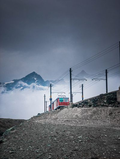 Low Angle View Of Train On Mountain Against Cloudy Sky