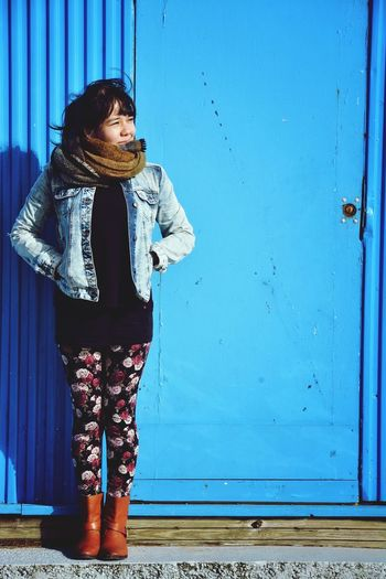 Full length of young woman standing against blue door