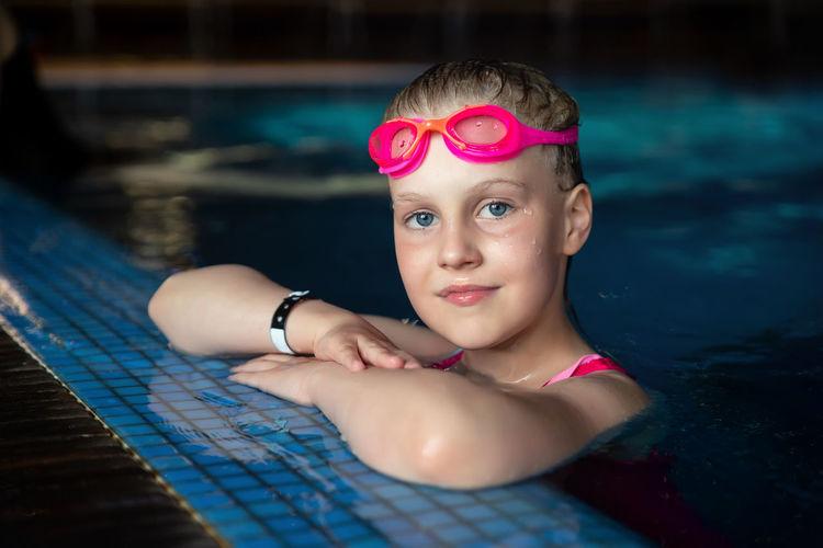 Portrait of teenage girl swimming in pool