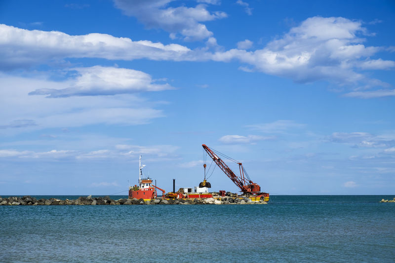 Mid distance view of crane making rocky groynes on sea against blue sky