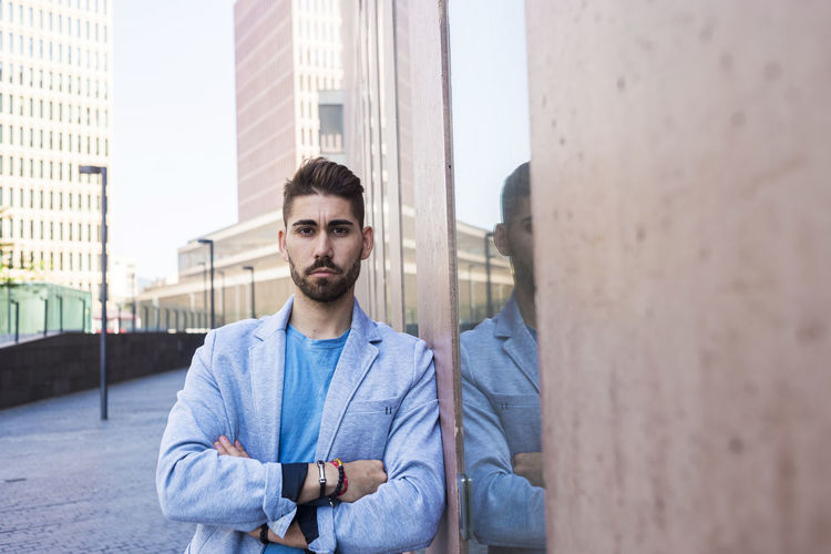 Portrait of young man standing against buildings in city