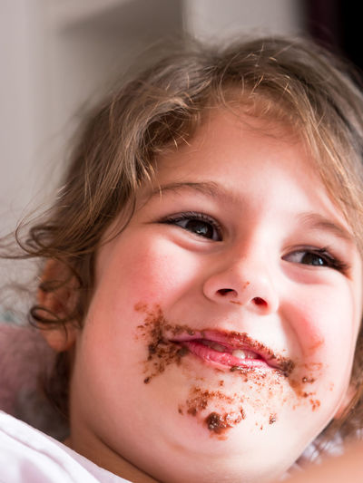 Cute messy with chocolate caucasian girl smiling Indoors  Child Portrait Childhood Headshot Front View Innocence Messy Chocolate Eating Small Little Caucasian Girl Kid Face Dirty Dessert Expression Beautiful Happy Cheerful Adorable Toddler  Cake Pretty Joy Smile Smiling