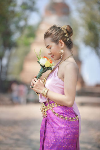 Woman in traditional clothing smelling flowers outdoors