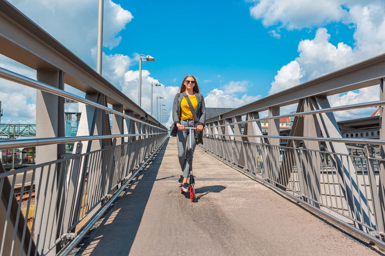 Low angle view of girl riding push scooter over footbridge