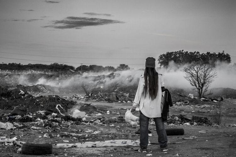 Rear view of woman standing against junkyard