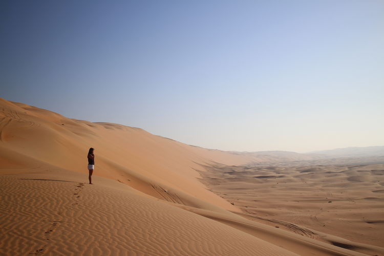 EyEmNewHere Sand Desert Sand Dune Arid Climate One Person Outdoors Clear Sky Heat - Temperature Adventure Landscape Nature Day Full Length People Adults Only Adult Only Men Lost In The Landscape