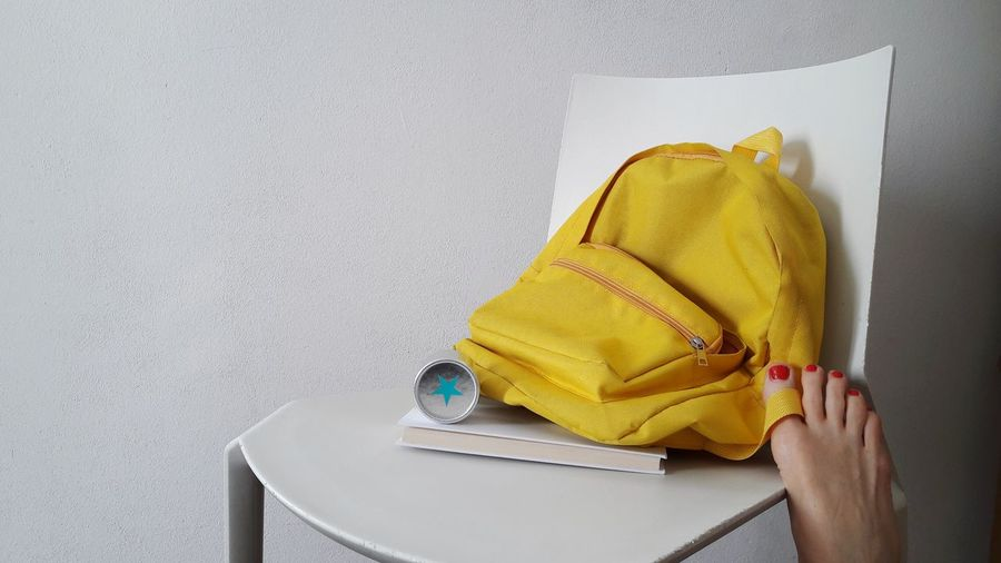 Low section of woman by backpack and book on chair against white wall