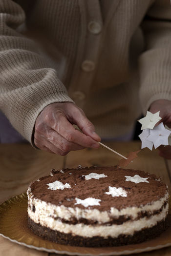 Midsection of person with cake on table