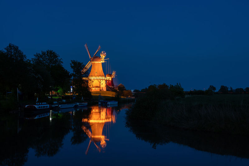 Greetsiel twin mill, Germany. Eastfrisian Greetsiel Greetsiel, Germany Wind Power Windmill Windmills Architecture Belief Blue Building Exterior Built Structure Dusk Eastfrisia Germany Illuminated Lake Lower Saxony Nature Night No People Plant Reflection Religion Sky Smock Mill Spirituality Tree Twin Mill Twin Mills Wadden Sea Water Waterfront