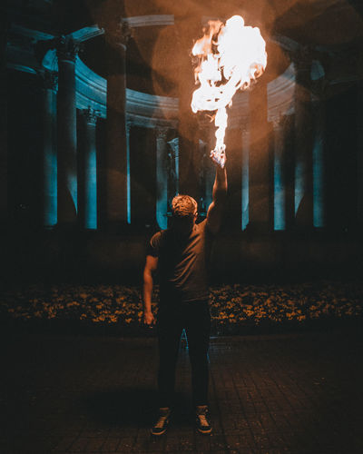 Man Holding Fire While Standing On Road At Night