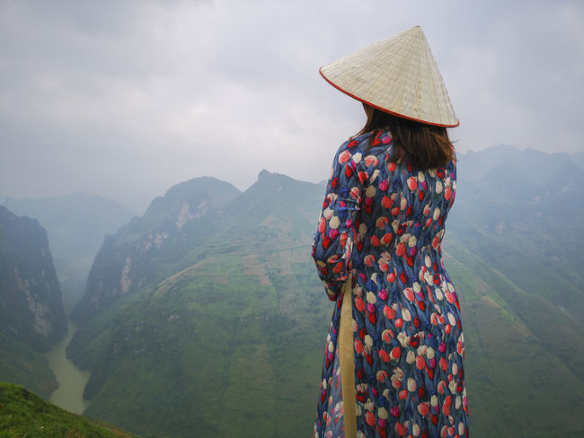 Young Vietnamese women facing and pose for camera with stunning view of the Nho Que river surrounded by mountains from the Ma Pi Leng pass in northern Vietnam Mountain Cloudy Green Color Meo Vac Vietnam Vietnamese Adult Ao Dai Beauty In Nature Day Hat Landscape Leisure Activity Lifestyles Looking At View Mountain Mountain Range Nature Non-urban Scene One Person Outdoors People Pose Real People Rear View Scenics - Nature Sky Standing Sunrise Three Quarter Length Traditional Dress Tranquil Scene Tranquility Valley Women