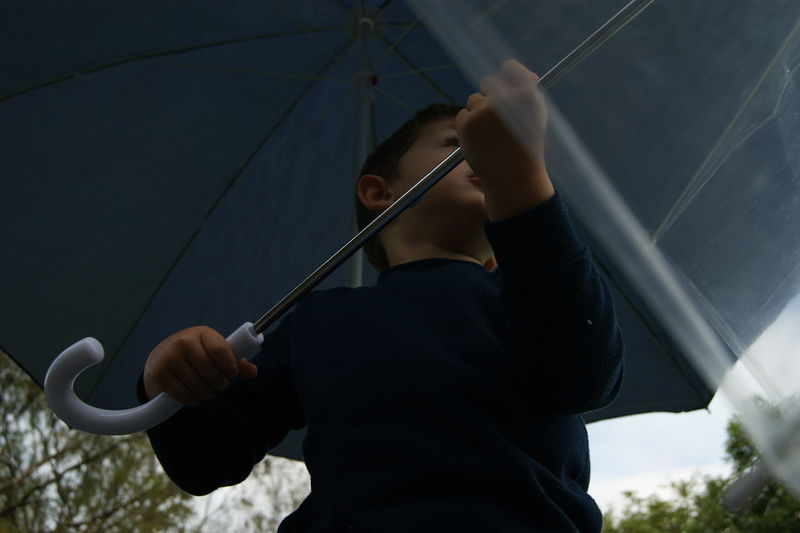 Low Angle View Of Boy Holding Umbrella