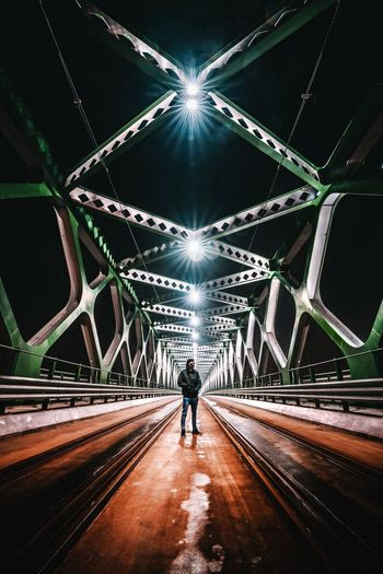 Mature Man Standing On Illuminated Bridge At Night