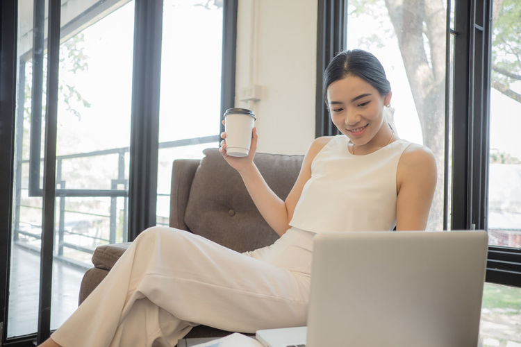 Young woman having coffee while sitting on chair in office