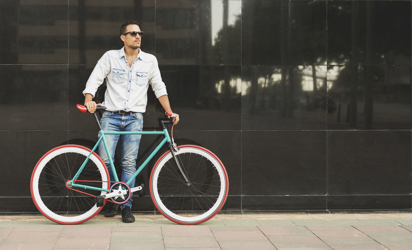 Full length of man standing by bicycle against building