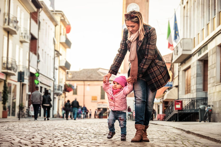 Mother assisting daughter in walking on street