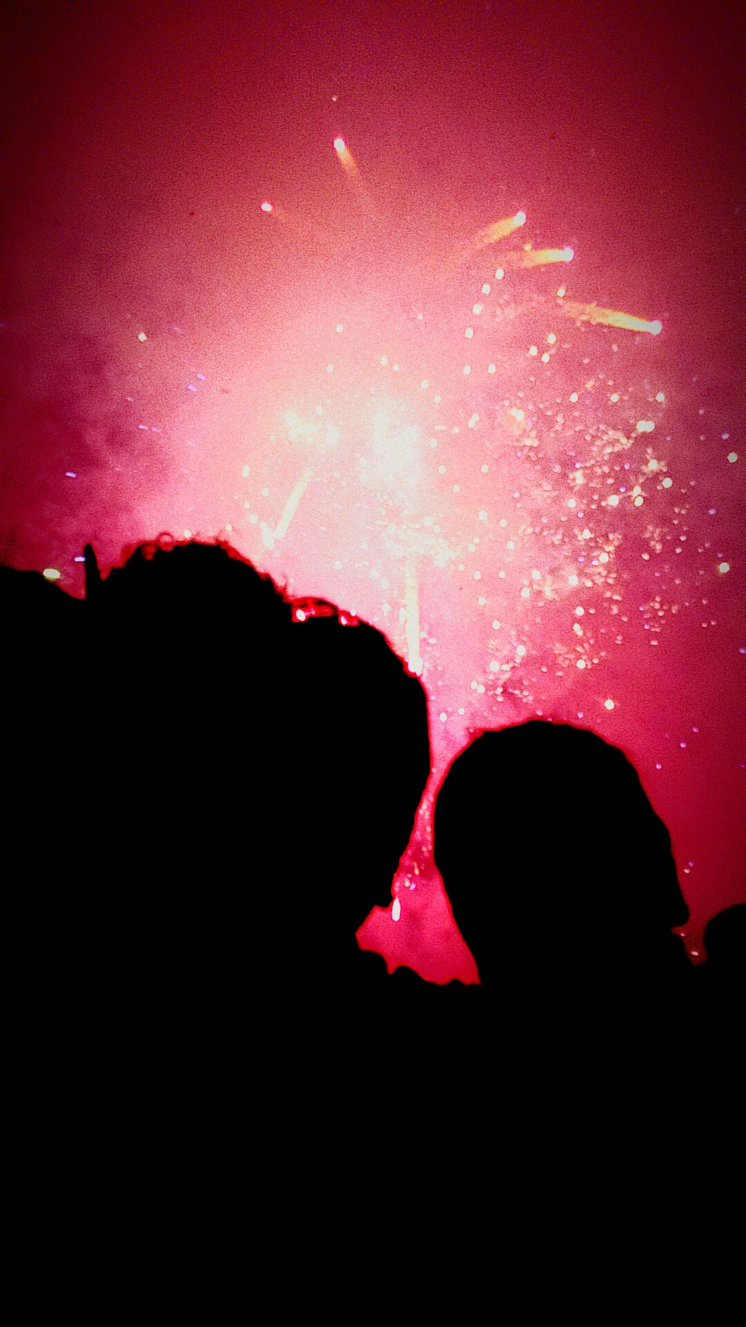 night, silhouette, illuminated, red, sky, dark, celebration, pink color, arts culture and entertainment, event, unrecognizable person, indoors, lifestyles, firework display, leisure activity, glowing, light - natural phenomenon, purple