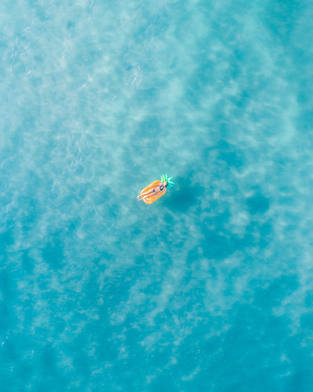 Drone view of woman relaxing on raft in sea