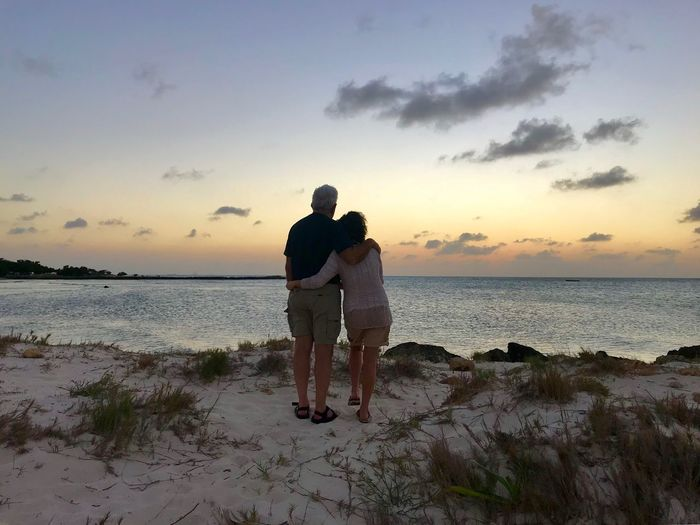 Rear View Of Senior Couple Standing At Beach During Sunset