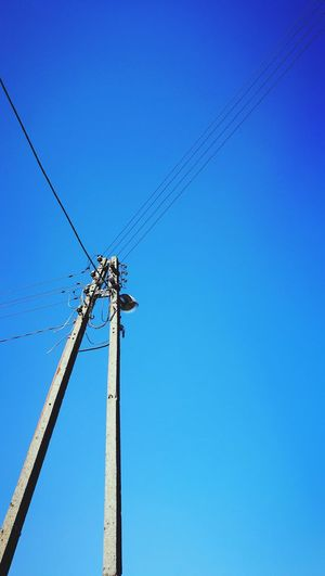 Electricity  Technology Blue Low Angle View Fuel And Power Generation Clear Sky No People Power Supply Connection Sky Business Finance And Industry Day Outdoors Electricity Pylon Nature Telegraph