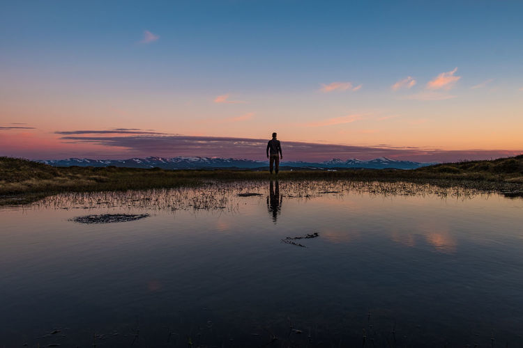 Rear view of man standing by lake against sky during sunset