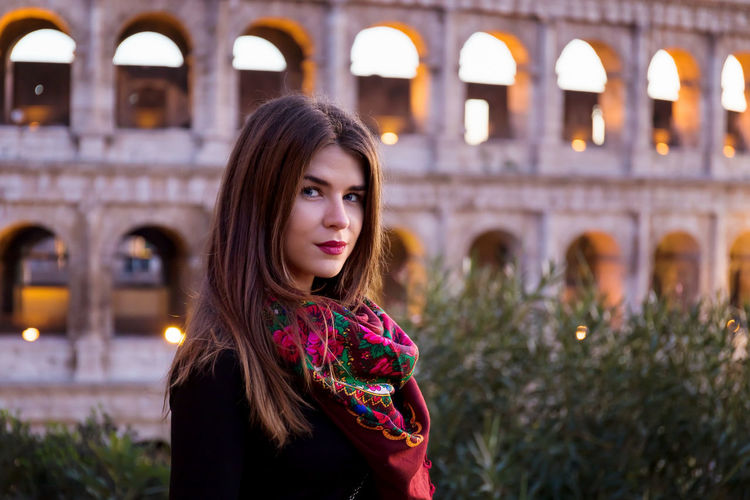 Portrait of beautiful woman standing against historical building