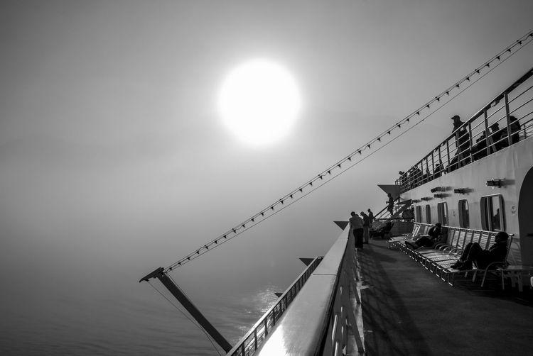 People On Ship Deck In Ocean Against Sky