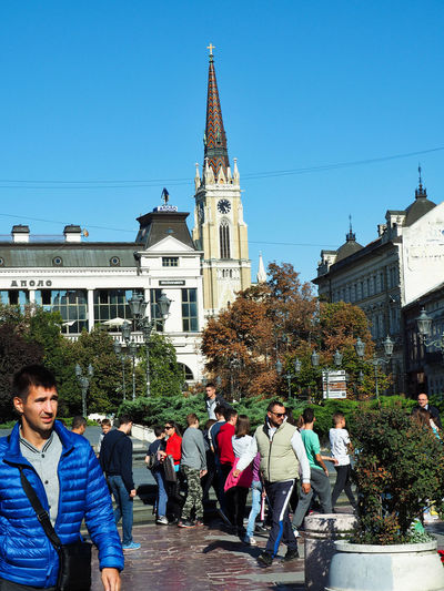 European Cities Building Exterior Built Structure Sunlight Facades Public Places Architecture Clear Blue Sky Travel Destinations Street Photography Outdoors Balkans Europe Eastern Europe Serbia Novi Sad Real People Day Men Women Place Of Worship Tower Religion Autumn colors Crowd Nature Tree