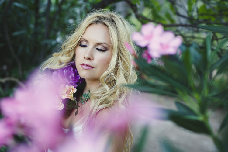 Bucolic scene portrait of young beautiful blond Caucasian female with closed eyes surrounded by pink flowers and green leaves in the countryside. Beautiful Woman Beauty Blond Hair Contemplation Flower Flower Head Flowering Plant Fragility Hair Hairstyle Leisure Activity Long Hair Nature One Person Outdoors Pink Color Plant Portrait Selective Focus Teenager Vulnerability  Women Young Adult Young Women