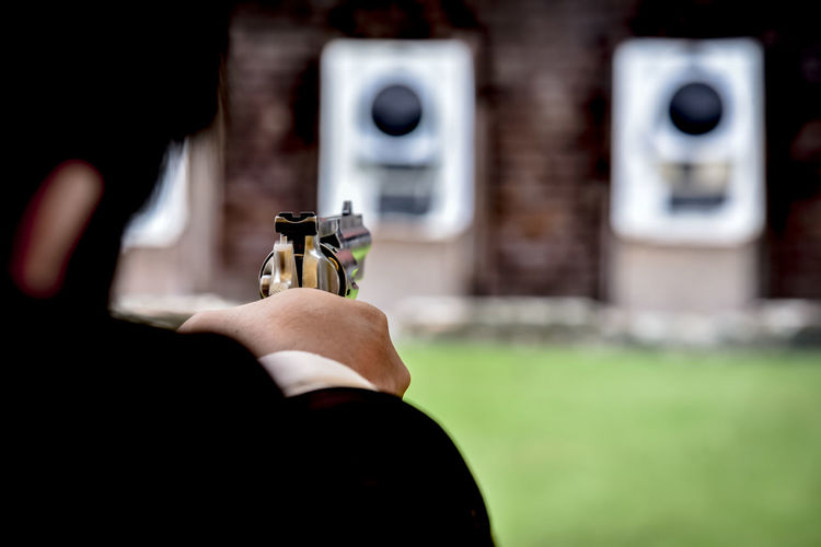 Close-up of man aiming gun during target shooting