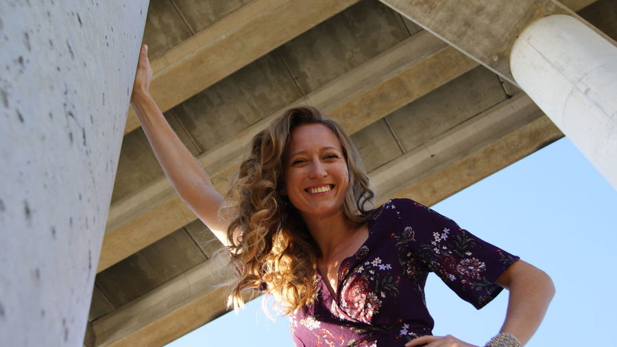 Low angle portrait of smiling young woman standing below bridge