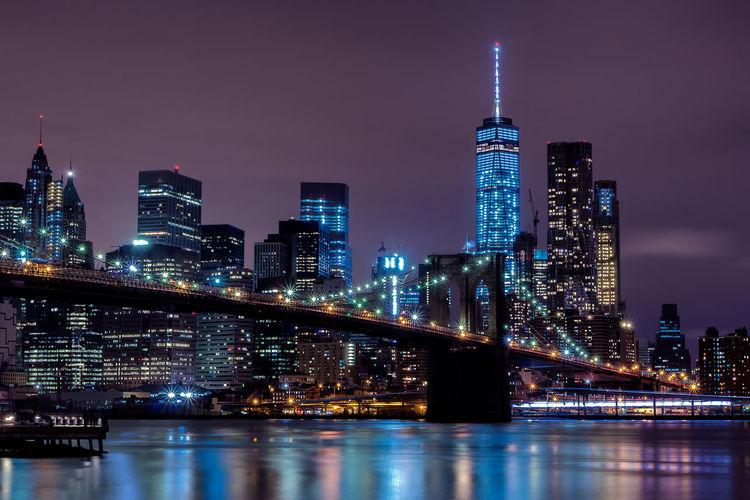 Illuminated buildings and brooklyn bridge against sky at night