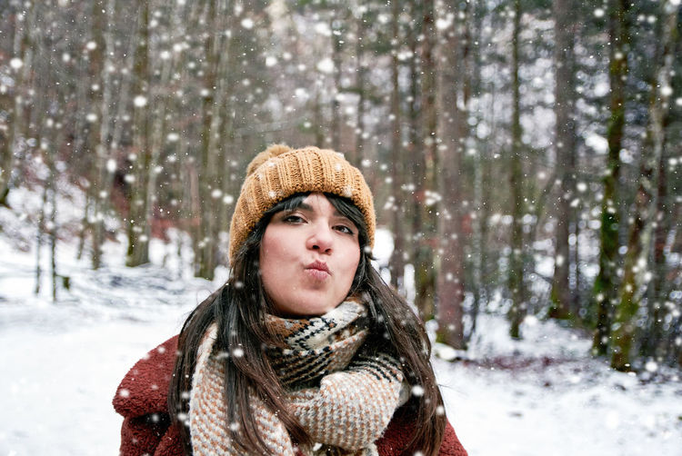 Portrait of a young woman during snowfall. winter clothes, sending a kiss.