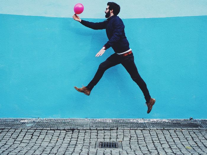Side view of man holding balloon jumping on footpath against wall