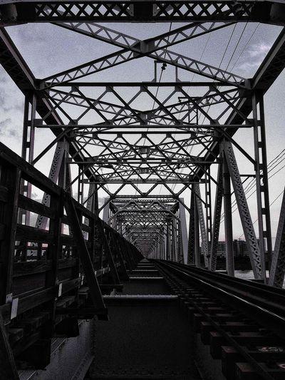 Long empty metallic bridge against the sky