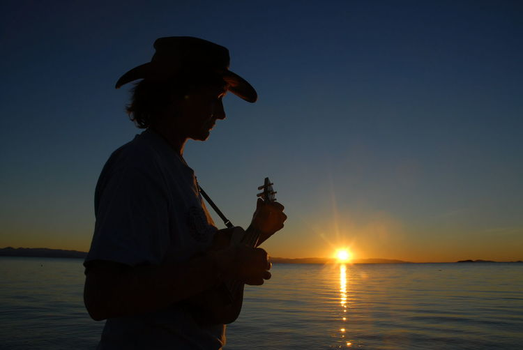 Woman playing ukulele by sea against sky during sunset